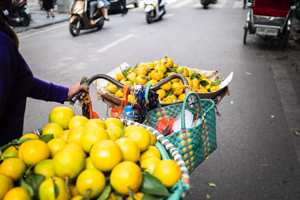 Bycle market sellers loaded with oranges for sale in Hanoi